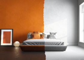 ett sovrum där ena halvan av rummet är vitt och andra halvan orange