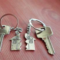 Två nycklar på rad bakgrund med varsin nyckelring med hänge i form av hus delat i mitten