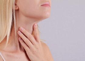kvinna känner utanpå sin hals