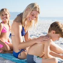 Mamma smörjer in sina barn på solig strand