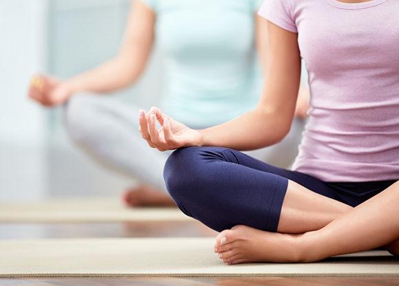 två personer på matta utövar enklare yoga