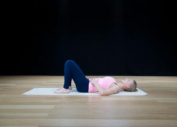 Enkel övning mot smartphone-nacke. Sara Ström ligger på golvet på yogamatta