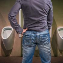 man i jeans står vid pissoar