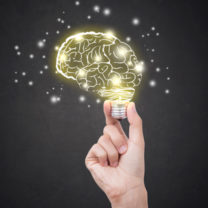 hand håller i animerad hjärna som lyser