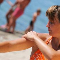 kvinna smörjer in sig på badstrand och barn i bakgrunden