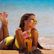 brun kvinna i gul bikini vid strandkant med röd drink