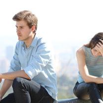 par sitter sorgsna och frånvända på mur