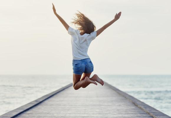Kvinna som hoppar på brygga
