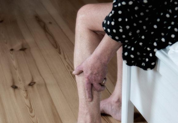 äldre kvinna på sängkant håller om sin vad