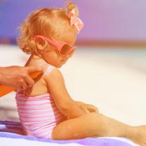 mamma smörjer in tvåårig dotter på stranden