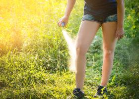 kvinna sprayar sina ben med myggmedel