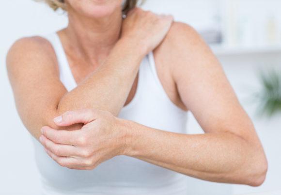 kvinna håller sig om armen
