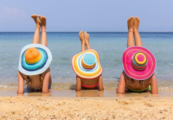 tre kvinnor med solhatt solar vid strandkanten