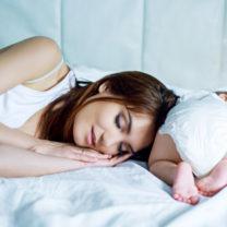 mamma sover bredvid bebis i blöja