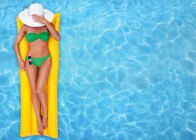 kvinna på gul madrass i pool
