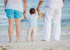 Två vuxna håller ett barn i handen