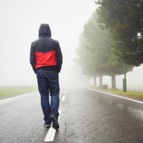 ensam man sedd bakifrån går mitt i väg i regn