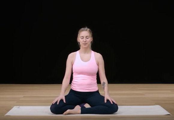 Kvinna på yogamatta gör andningsövning mot stress