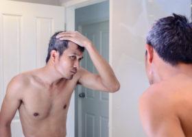 Gråhårig man speglar sig