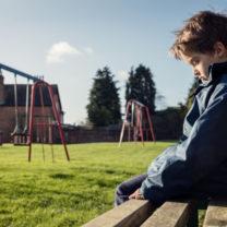 ledsen pojke sitter ensam på bänk