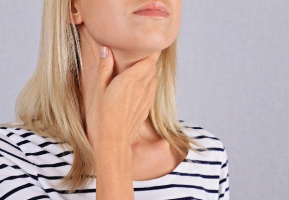 kvinna håller hand över halsen