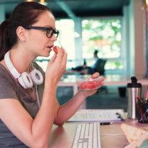 kvinna äter vid datorn