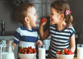 barn matar varandra med jordgubbar