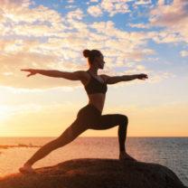kvinna i yogapose i solnedgång