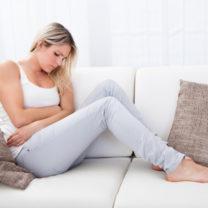 tjej sitter i soffa och håller sig om magen