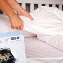 någon byter lakan i en säng och tvättmaskin