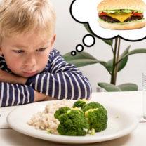pojke framför tallrik med broccoli drömmer om en hamburgare