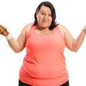 överviktig kvinna med äpple och macka i handen
