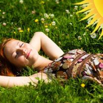 kvinna ligger i gräset och solar