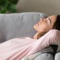 kvinna soml ligger i en soffa