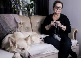 Berith sitter i soffan med hundarna och stickar