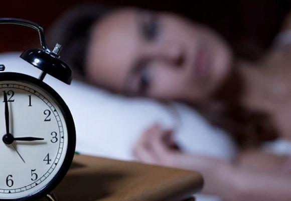 kvinna stirrar på väckarklockan