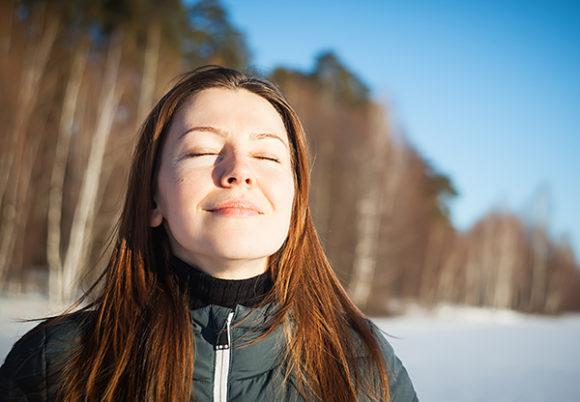 ung kvinna i vinterlandskap blundar och andas