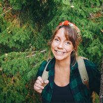 Emma V Larsson intill trädstam i skogsmiljö