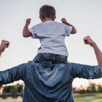 liten kille på sin pappas axlar - båda spänner armarna som om de känner sig kraftfulla
