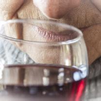 närbild äldre kvinnas mun nära glas med rött vin