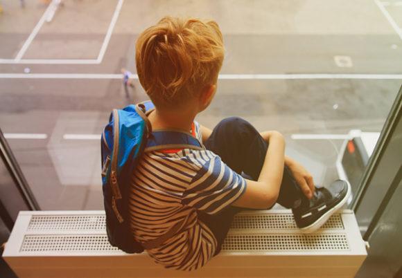 Liten pojke sitter i fönster och tittar ut