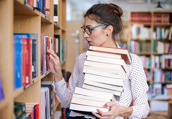Kvinna håller trave böcker på bibliotek