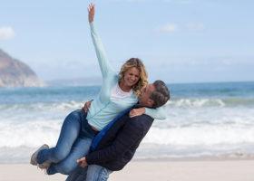 Man lyfter lekfullt upp kvinna på strand