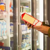 Manshand håller neutral mjölkförpackning intill butikshyllor med mejeriprodukter