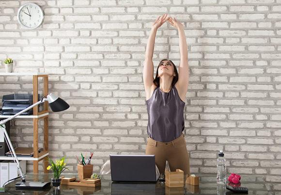 kvinna utför rörelse vid skrivbord