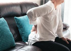 kvinna på soffa tar sig åt ryggen
