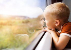 Pojke tittar ut genom tågfönster