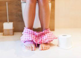 Kvinna sitter på toaletten