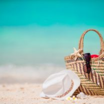 stråväska på stranden med hatt och solglasögon