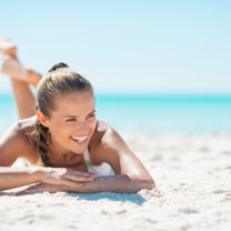 Kvinna som solar på stranden